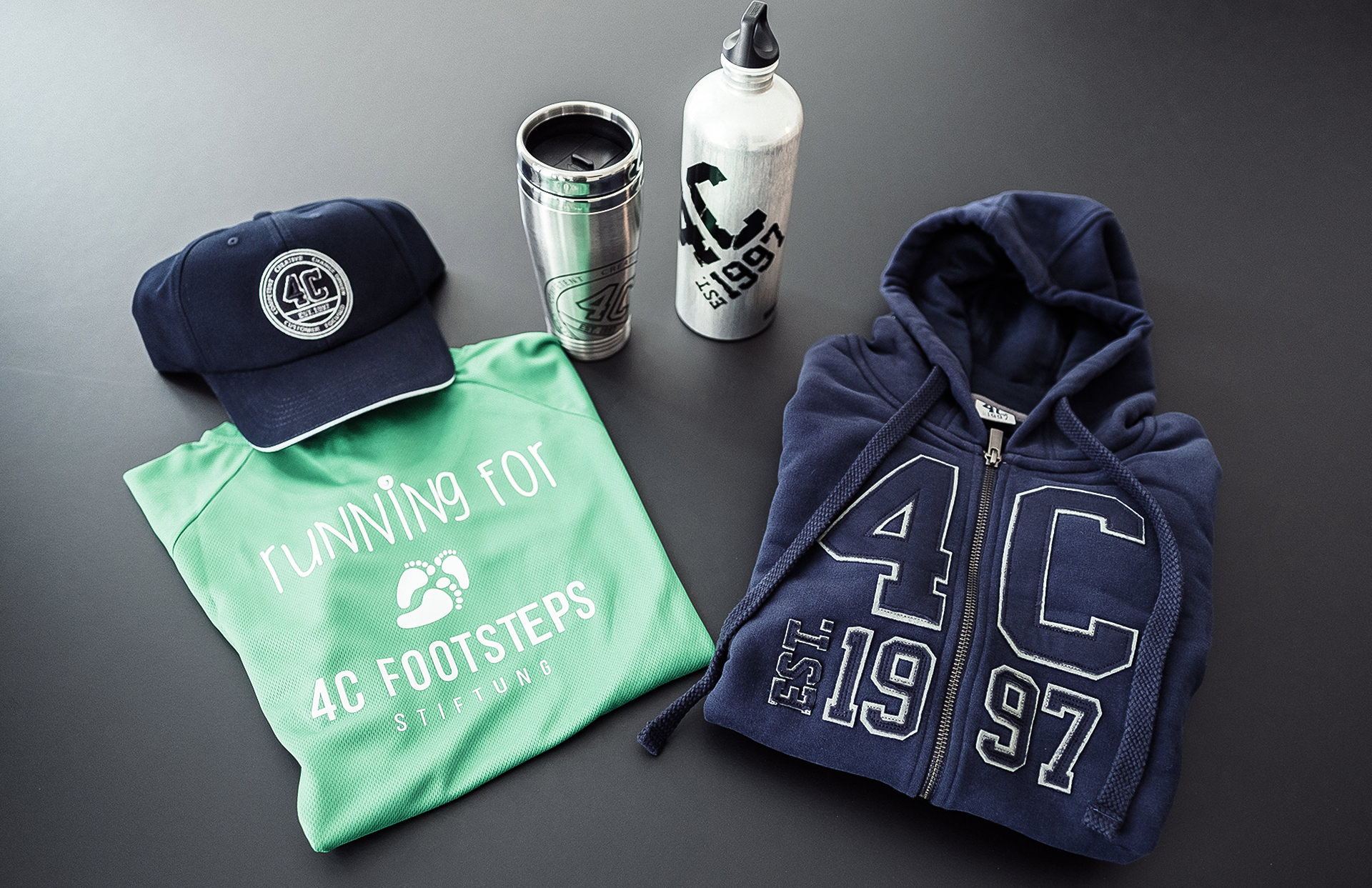 Overview of 4C collection design products including branded hoodies, individual shirts, caps and coffe mugs designed by LAKE5 in Hannover.